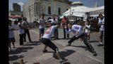 En esta imagen del 1 de septiembre de 2019, gente practicando capoeira en el mercado ribereño de Ver-o-Peso en Belén, Brasil. La capoeira es un arte marcial afrobrasileño que combina elementos de danza, acrobacias y música. Fue desarrollada por esclavos africanos en Brasil. (AP Foto/Rodrigo Abd)