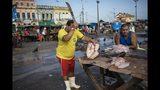 En esta imagen del 7 de septiembre de 2019, un vendedor prepara pescado para los clientes en su puesto callejero del mercado ribereño de Ver-o-Peso en Belém, Brasil. El mercado al aire libre es el símbolo de una ciudad antes identificada con el comercio de caucho, y conocida ahora como capital gastronómica de la Amazonía. (AP Foto/Rodrigo Abd)