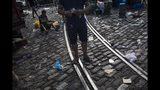 En esta imagen del 7 de septiembre de 2019, un vendedor cuenta dinero mientras otro recoge bayas de azaí del suelo en el mercado ribereño de Ver-o-Peso en Belén, Brasil. La demanda global de la fruta ha crecido con rapidez en el siglo XXI, de modo que el árbol se cultiva principalmente con ese fin. (AP Foto/Rodrigo Abd)