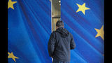 A man walks through a sliding door with the European Union stars outside EU headquarters in Brussels, Sunday, Oct. 13, 2019. Technical talks on Brexit continued in Brussels over the weekend with European Union Brexit negotiator Michel Barnier due to brief EU ambassadors. (AP Photo/Virginia Mayo)
