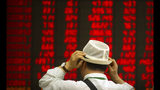 FILE - In this Sept. 5, 2019, file photo, an investor adjusts his hat as he monitors stock prices at a brokerage house in Beijing. Asian stock markets have risen after Washington and Beijing announced a truce on tariff hikes in a trade war. Benchmarks in Shanghai, Hong Kong and Seoul advanced. Japanese markets were closed for a holiday. (AP Photo/Mark Schiefelbein, File)