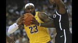 Los Angeles Lakers' LeBron James, left, in action against Brooklyn Nets' Theo Pinson, right, during the NBA China Games 2019 in Shenzhen in south China's Guangdong province on Saturday, Oct. 12, 2019.(Color China Photo via AP)
