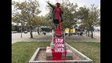 """A sign reading """"stop celebrating genocide"""" sits at the base of a statue of Christopher Columbus on Monday, Oct. 14, 2019, in Providence, R.I., after it was vandalized with red paint on the day named to honor him as one of the first Europeans to reach the New World. The statue has been the target of vandals on Columbus Day in the past. (AP Photo/Michelle R. Smith)"""