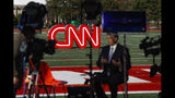 A journalist records video near a CNN sign on an athletic field outside the Clements Recreation Center where the CNN/New York Times will host the Democratic presidential primary debate at Otterbein University, Monday, Oct. 14, 2019, in Westerville, Ohio. (AP Photo/John Minchillo)
