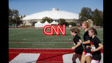 Student athletes pass a CNN sign on an athletic field outside the Clements Recreation Center where the CNN/New York Times will host the Democratic presidential primary debate at Otterbein University, Monday, Oct. 14, 2019, in Westerville, Ohio. (AP Photo/John Minchillo)