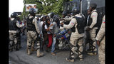 Police surround a motorcycle that tried to drive through a police barricade on the road leading to the home of President Jovenel Moïse, in Petion-Ville, Port-au-Prince, Haiti, Sunday, Oct. 13, 2019. Thousands of Haitians joined a largely peaceful protest called by the art community Sunday to demand Moïse resign, increasing pressure on the embattled leader after nearly a month of marches that have shuttered schools and businesses.(AP Photo/Rebecca Blackwell)