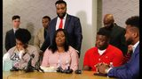Amber Carr, left, wipes a tear as her sister Ashley Carr, center, talks about their sister, Atatiana Jefferson, as their brother, Adarius Carr, right and attorney Lee Merritt, standing, listen during a news conference Monday, Oct. 14, 2019 in downtown Dallas. The family of the 28-year-old black woman who was shot and killed by a white police officer in her Fort Worth home as she played video games with her 8-year-old nephew expressed outrage that the officer has not been arrested or fired. (Irwin Thompson/The Dallas Morning News via AP)