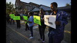 """Protesters gather outside the house, right, where Atatiana Jefferson was shot Saturday and killed by police, during a community vigil for Jefferson on Sunday, Oct. 13, 2019, in Fort Worth, Texas. A white police officer who killed the black woman inside her Texas home while responding to a neighbor's call about an open front door """"didn't have time to perceive a threat"""" before he opened fire, an attorney for Jefferson's family said. (Smiley N. Pool/The Dallas Morning News via AP)"""