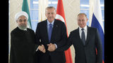 FILE - This Sept. 16, 2019 file photo, from left: Iranian President Hassan Rouhani, Turkish President Recep Tayyip Erdogan and Russian President Vladimir Putin shake hands during their meeting in Ankara, Turkey. America maintains some 1,000 troops in Syria who work alongside the Kurdish fighters. America's foes -- Assad, Russia, and Iran -- all stand to gain from a U.S. troop withdrawal in Syria. (AP Photo/Pavel Golovkin, Pool, File)
