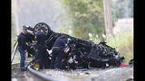 Emergency personnel survey the remains of a Porsche SUV that plummeted off an overpass onto train tracks below Sunday afternoon, where it burst into flames, killing two teenagers and sending a third to a hospital with serious injuries. in Pearl River, NY, Sunday, October 13, 2019. (Kevin Wexler/NorthJersey.com via AP)