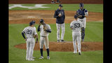New York Yankees shortstop Didi Gregorius, third from left, talks with third baseman Gio Urshela (29) and second baseman Gleyber Torres as relief pitcher Zack Britton (53) enters the game replacing pitcher Adam Ottavino (0) during the eighth inning of Game 3 of baseball's American League Championship Series against the Houston Astros, Tuesday, Oct. 15, 2019, in New York. (AP Photo/Seth Wenig)