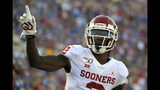FILE - In this Sept. 14, 2019, file photo,Oklahoma wide receiver CeeDee Lamb celebrates after scoring a touchdown during the first half of an NCAA college football game against UCLA, in Pasadena, Calif. Lamb was selected to the AP Midseason All-America NCAA college football team, Tuesday, Oct. 15, 2019. (AP Photo/Mark J. Terrill)
