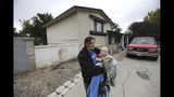 Alanna Mabey holds her grandson in front of her home, Wednesday, Oct. 9, 2019, in West Valley City, Utah. Paul Petersen sold the house this spring as complaints mounted from neighbors in the working-class area in suburban Salt Lake City, said new owner Mabey. Authorities say Petersen used homes like this one to lodge pregnant women from the Marshall Islands who were offered money to come to the U.S. to give up their children for adoption. Petersen, the assessor of Arizona's most populous county, was charged in Utah, Arizona and Arkansas with counts including human smuggling, sale of a child, fraud, forgery and conspiracy to commit money laundering. (AP Photo/Rick Bowmer)