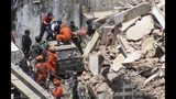 Firefighters rescue a woman from a building that collapsed in Fortaleza, Ceara state, Brazil, Tuesday, Oct. 15, 2019. A seven-story building collapsed Tuesday in the northeastern city of Fortaleza, killing at least one person. City authorities informed several others are under the debris, and some of them are communicating with relatives and rescue teams by telephone. (Kleber Goncalves/Futura Press via AP)