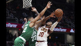 Cleveland Cavaliers' Darius Garland (10) goes up for a shot against Boston Celtics' Vincent Poirier (77) and Grant Williams (12) during the second half of an NBA preseason basketball game Tuesday, Oct. 15, 2019, in Cleveland. The Celtics won 118-95. (AP Photo/Ron Schwane)