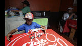 A child plays with a fire engine at a restaurant that reopened for business as Ecuadorians returned to a semblance of normality after nearly two weeks of protests, in Quito Ecuador, Monday, Oct. 14, 2019. Protests over an austerity package blocked roads, shuttered businesses from dairies to flower farms and halved Ecuador's oil production, forcing a temporary halt to the country's most important export. (AP Photo/Dolores Ochoa)