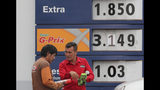 An attendant shows an automotive product to a driver in front of a display with new fuel prices at a gas station in Quito, Ecuador, Tuesday, Oct. 15, 2019. The recent strike that paralyzed the Andean nation for almost two weeks, has left a gaping hole in Ecuador's economy, this after President Lenin Moreno called back his elimination of fuel subsidies which provoked the violent protests. (AP Photo/Dolores Ochoa)