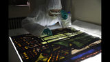 In this photo taken on Wednesday, Oct. 9, 2019, Glass specialist Claudine Loisel checks the Notre Dame cathedral's stained-glass windows in a lab at Champs-sur-Marne, west of Paris. Scientists at the French government's Historical Monuments Research Laboratory are using these objects as clues in an urgent and vital task, working out how to safely restore the beloved Paris cathedral and identify what perils remain inside in a race against the clock. (AP Photo/Francois Mori)