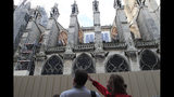 """People walk by Notre Dame cathedral Tuesday, Oct. 15, 2019 in Paris. French Culture Minister Franck Riester said the melted, twisted scaffolding atop Notre Dame Cathedral will be removed """"in coming weeks"""" to allow restoration work to begin. It's been six months since fire gutted the medieval structure, which was under renovation at the time and crisscrossed with scaffolding where the spire once stood. (AP Photo/Michel Euler)"""