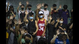 A demonstrator wearing Houston Rockets jersey holds up his hand with fellow demonstrators during a rally at the Southorn Playground in Hong Kong, Tuesday, Oct. 15, 2019. Protesters in Hong Kong have thrown basketballs at a photo of LeBron James and chanted their anger about comments the Los Angeles Lakers star made about free speech during a rally in support of NBA commissioner Adam Silver and Houston Rockets general manager Daryl Morey, whose tweet in support of the Hong Kong protests touched off a firestorm of controversy in China. (AP Photo/Mark Schiefelbein)