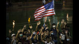 A demonstrator holds a U.S. flag during a rally at the Southorn Playground in Hong Kong, Tuesday, Oct. 15, 2019. Protesters in Hong Kong have thrown basketballs at a photo of LeBron James and chanted their anger about comments the Los Angeles Lakers star made about free speech during a rally in support of NBA commissioner Adam Silver and Houston Rockets general manager Daryl Morey, whose tweet in support of the Hong Kong protests touched off a firestorm of controversy in China. (AP Photo/Mark Schiefelbein)