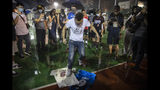 A demonstrator stomps on Lebron James jerseys during a rally at the Southorn Playground in Hong Kong, Tuesday, Oct. 15, 2019. Protesters in Hong Kong have thrown basketballs at a photo of LeBron James and chanted their anger about comments the Los Angeles Lakers star made about free speech during a rally in support of NBA commissioner Adam Silver and Houston Rockets general manager Daryl Morey, whose tweet in support of the Hong Kong protests touched off a firestorm of controversy in China. (AP Photo/Mark Schiefelbein)
