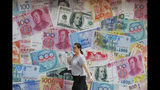 FILE - In this Aug. 6, 2019, file photo, a woman walks by a money exchange shop decorated with different countries currency banknotes at Central, a business district in Hong Kong. The IMF's latest World Economic Outlook comes on the eve of meetings in Washington this week of the IMF and its sister lending organization, the World Bank. (AP Photo/Kin Cheung, File)