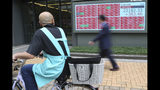 A man looks at an electronic stock board of a securities firm in Tokyo, Tuesday, Oct. 15, 2019. On Tuesday, shares are mixed in Asia after a wobbly day of trading on Wall Street. Japan's Nikkei 225 index jumped 1.8% as it reopened from a public holiday and investors caught up on the news of a preliminary trade deal between China and the U.S. (AP Photo/Koji Sasahara)