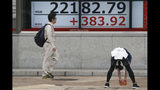 A man stretches in front of an electronic stock board of a securities firm in Tokyo, Tuesday, Oct. 15, 2019. On Tuesday, shares are mixed in Asia after a wobbly day of trading on Wall Street. Japan's Nikkei 225 index jumped 1.8% as it reopened from a public holiday and investors caught up on the news of a preliminary trade deal between China and the U.S. (AP Photo/Koji Sasahara)