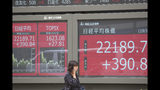 A woman walks by an electronic stock board of a securities firm in Tokyo, Tuesday, Oct. 15, 2019. On Tuesday, shares are mixed in Asia after a wobbly day of trading on Wall Street. Japan's Nikkei 225 index jumped 1.8% as it reopened from a public holiday and investors caught up on the news of a preliminary trade deal between China and the U.S. (AP Photo/Koji Sasahara)