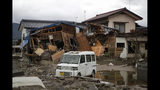 A vehicle sits in front of a home destroyed by Typhoon Hagibis Tuesday, Oct. 15, 2019, in Nagano, Japan. More victims and more damage have been found in typhoon-hit areas of central and northern Japan, where rescue crews are searching for people still missing. (AP Photo/Jae C. Hong)