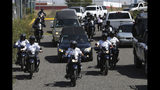 Police escort a caravan of funeral vehicles transporting the bodies of Mexican police officers killed in an apparent cartel ambush, in Morelia, Mexico, Tuesday, Oct. 15, 2019. The families of the 13 slain police officers gathered to mourn their loved ones outside a funeral home in the western state of Michoacan on Tuesday, many of them angry at the government and police chiefs they believe sent them to a certain death. (AP Photo/Marco Ugarte)
