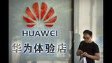 """FILE - In this May 29, 2019, file photo, a man uses his smartphone outside of a shop selling Huawei products at a shopping mall in Beijing. The New York Times reports the Trump administration plans to issue licenses to U.S. companies to supply """"non-sensitive goods"""" to Chinese tech giant Huawei in a move that might help to cool tensions ahead of trade talks. (AP Photo/Mark Schiefelbein, File)"""
