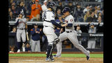 Houston Astros' Michael Brantley, right, scores past New York Yankees catcher Gary Sanchez on a sacrifice fly by Yuli Gurriel during the seventh inning in Game 3 of baseball's American League Championship Series Tuesday, Oct. 15, 2019, in New York. (AP Photo/Matt Slocum)