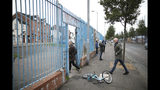 In this Tuesday, Oct. 15, 2019 photo tourists with Belfast Political Tours walk into a Loyalist area in west Belfast, Northern Ireland. Fears about a return to the violence that killed more than 3,500 people over three decades have made Northern Ireland the biggest hurdle for U.K. and EU officials who are trying to hammer out a Brexit divorce deal. (AP Photo/Peter Morrison)