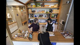 In this Wednesday, Oct. 9, 2019 photo, bloom tenders behind the front counter at the Village Bloomery, a marijuana retail shop, assist a customer in Vancouver, B.C. Sales in the first year of legalization are expected to total $1 billion, a sizable amount but still dwarfed by an illegal market still estimated at $5 billion to $7 billion. (AP Photo/Elaine Thompson)