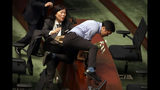 A security officer tries to stop pro-democracy lawmaker Au Nok-hin from climbing on a desk as Hong Kong Chief Executive Carrie Lam leaves a question and answer session with lawmakers at the Legislative Council in Hong Kong, Thursday, Oct. 17, 2019. (AP Photo/Mark Schiefelbein)