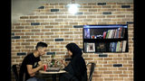 """In this Monday, Oct. 7, 2019 photo, two Afghan refugees eat at an Afghan cafe in downtown Tehran, Iran. More than 3 million Afghans including as many as 2 million who entered without legal permission, live in the Islamic Republic, according to United Nations estimates. Fatemeh Jafari, a 21-year-old Afghan refugee, hopes her Telma, or """"Dream,"""" Café in Tehran will help bridge the divides and xenophobia Afghans can face in Iran. (AP Photo/Ebrahim Noroozi)"""