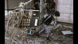 A woman makes her way though the mud and debris from Typhoon Hagibis, with a phone hanging on the wire, front, at Hoyasu district in Nagano, central Japan Wednesday, Oct. 16, 2019. The typhoon hit Japan's main island on Saturday with strong winds and historic rainfall that caused more than 200 rivers to overflow, leaving thousands of homes flooded, damaged or without power. (Koji Sengoku/Kyodo News via AP)