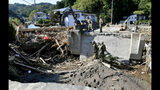 Japan's Self-Defense Forces' members work to remove piled driftwood at a bridge after Typhoon Hagibis hits the town in Marumori, Miyagi prefecture, northern Japan Wednesday, Oct. 16, 2019. The typhoon hit Japan's main island on Saturday with strong winds and historic rainfall that caused more than 200 rivers to overflow, leaving thousands of homes flooded, damaged or without power. (Kyodo News via AP)