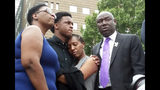 FILE - In this Sept. 10, 2018 file photo, Brandt Jean, center left, brother of shooting victim Botham Jean, hugs his sister Allisa Charles-Findley, during a news conference about the shooting of Botham Jean by Dallas Police Officer Amber Guyger, outside the Frank Crowley Courts Building in Dallas. He was joined by his mother, Allison Jean, left, and attorney Benjamin Crump, right. Guyger, who was fired soon after the shooting and charged with murder, said she mistook Jean's apartment for her own. She was convicted in early Oct. 2019 - a rare jury decision - and sentenced to 10 years in prison. (AP Photo/Ryan Tarinelli, File)