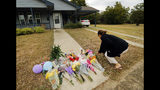 Anastasia Gonzalez, of Burleson, Texas, leaves a flowers on the front sidewalk of Atatiana Jefferson's home on E. Allen Ave in Fort Worth, Texas, Tuesday, Oct. 15, 2019. Jefferson, a black woman, was shot by a white police officer early Saturday, Oct. 12. (Tom Fox/The Dallas Morning News via AP)