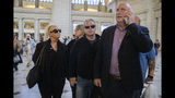 Charlotte Charles, left, mother of British teenager Harry Dunn, and her husband Bruce Charles, center arrive at Union Station in Washington, Tuesday, Oct. 15, 2019. The family of a British teenager killed in a car crash involving an American diplomat's wife was headed to the White House on Tuesday for a meeting with senior administration officials. On the phone is family spokesman Radd Seiger. (AP Photo/Manuel Balce Ceneta)