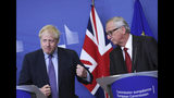 British Prime Minister Boris Johnson gestures as he stands alongside European Commission President Jean-Claude Juncker during a press point at EU headquarters in Brussels, Thursday, Oct. 17, 2019. Britain and the European Union reached a new tentative Brexit deal on Thursday, hoping to finally escape the acrimony, divisions and frustration of their three-year divorce battle. (AP Photo/Francisco Seco)