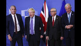 Britain's Brexit Secretary Stephen Barclay, British Prime Minister Boris Johnson, European Commission President Jean-Claude Juncker and European Union chief Brexit negotiator Michel Barnier, from left, pose for a photo during a press point at EU headquarters in Brussels, Thursday, Oct. 17, 2019. Britain and the European Union reached a new tentative Brexit deal on Thursday, hoping to finally escape the acrimony, divisions and frustration of their three-year divorce battle. (AP Photo/Francisco Seco)