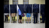 People use voting booths at a pooling station during general elections in Gibraltar, Thursday Oct. 17, 2019. An election for Gibraltar's 17-seat parliament is taking place Thursday under a cloud of uncertainty about what Brexit will bring for this British territory on Spain's southern tip. (AP Photo/Javier Fergo)