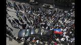"""The funeral procession accompanying the body of murdered community leader Josemano """"Badou"""" Victorieux to the cemetery passes by cars burnt during recent demonstrations in the Delmas area of Port-au-Prince, Haiti, Wednesday, Oct. 16, 2019. Funerals for 11 of at least 20 people killed were held in six cities, including the capital of Port-au-Prince, where at least two people were injured in a protest that broke out when presidential guards tried to block a road near where hundreds had gathered around the coffins of two victims. (AP Photo/Rebecca Blackwell)"""