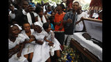 Family members grieve beside the coffin of one of the men killed during a month of demonstrations aimed at ousting Haitian President Jovenel Moïse, during a joint funeral for two victims in a public plaza near the National Palace in central Port-au-Prince, Haiti, Wednesday, Oct. 16, 2019. Funerals for 11 of at least 20 people killed were held in six cities. (AP Photo/Rebecca Blackwell)