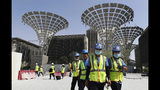 In this Oct. 8, 2019, photo, technicians walk at the three thematic districts at the under construction site of the Expo 2020 in Dubai, United Arab Emirates. (AP Photo/Kamran Jebreili)