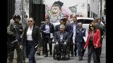 El presidente ecuatoriano Lenín Moreno llega a un encuentro con comerciantes afectados por protestas cerca de la Asamblea Nacional en Quito, Ecuador, el jueves 17 d octubre de 2019. (AP Foto/Dolores Ochoa)
